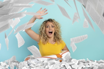 Blonde girl is surrounded by a lot of paper sheet and asks for help . concept of bureaucracy and overwork
