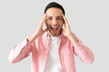 Good looking young man looking surprised and screaming with excitement in a studio